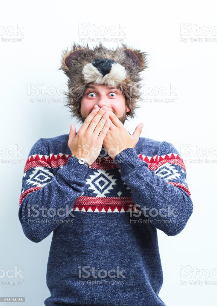 Man in winter outfit looking surprised Portrait of surprised young man in winter clothing covering his mouth with hand on white background Adult Stock Photo