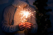 young caucasian man wearing knitted grey wollen sweater and white scarf holding sparkler in his hands at night with fir tree branch at background