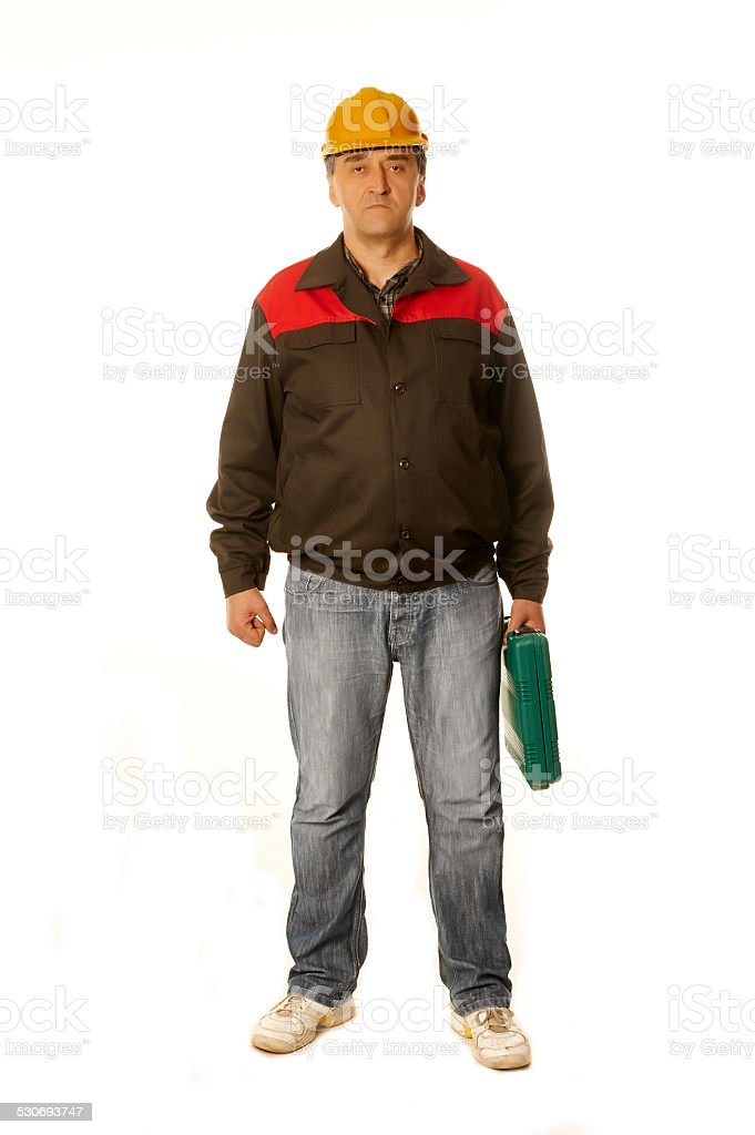 Man in work clothes, yellow helmet, protective jacket, green suitcase. stock photo