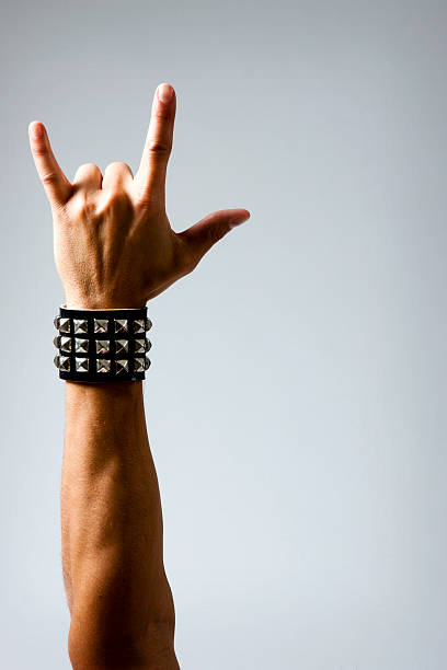 man in wristband making rock & roll hand symbol - rock music stock pictures, royalty-free photos & images
