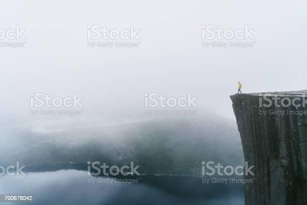 Photo of Man in yellow raincoat on the Preikestolen in fog in Norway