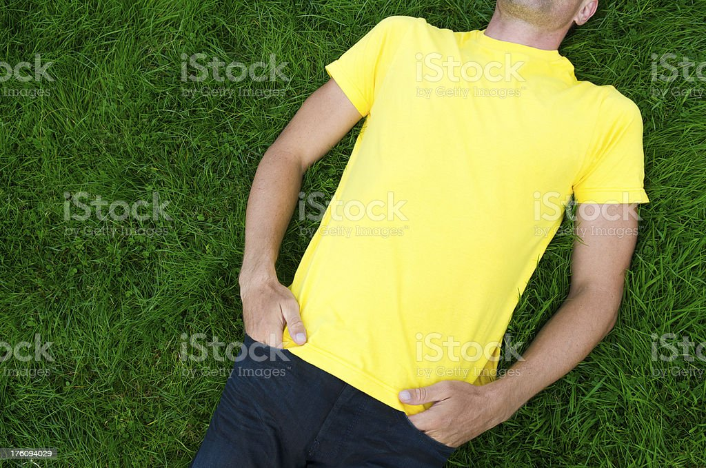 Man in Yellow T-Shirt Lies on Green Grass royalty-free stock photo