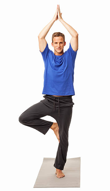 Man In Yoga Tree Pose - Isolated Full length portrait of healthy man doing yoga on exercise mat. Vertical shot. Isolated on white. yoga instructor stock pictures, royalty-free photos & images
