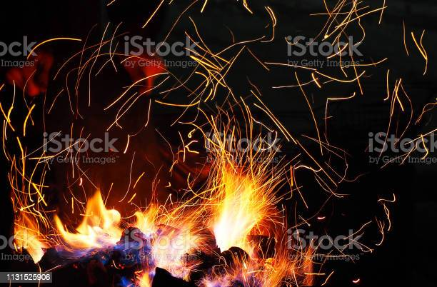 Photo of A man inflates the embers of a campfire, flame flashes and sparks, fire. Flame dance, evening barbecue. Scenic dark background