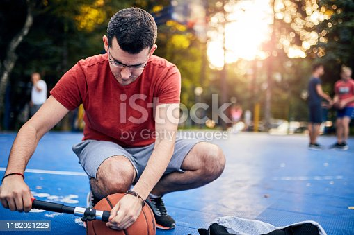 Man inflating basketball ball with a hand pump on the urban court.
