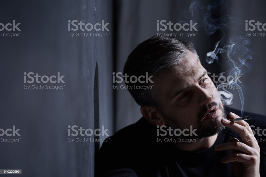 Man inhaling cigarette smoke stock photo