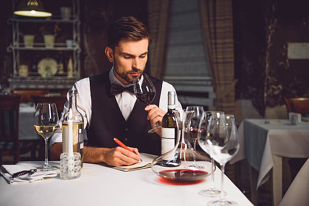 man inhaling sort of wine Professional sommelier smelling red drink from wineglass with pleasure critic stock pictures, royalty-free photos & images