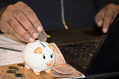 istock Man inserting coin in piggy bank 1129643421