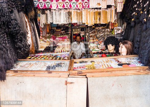 Trichy, Tamil Nadu, India - February 2020: An Indian shopkeeper selling wigs and jewelry in his shop in the markets of Tiruchirappalli.