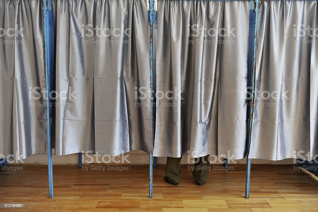 Man inside a voting booth stock photo