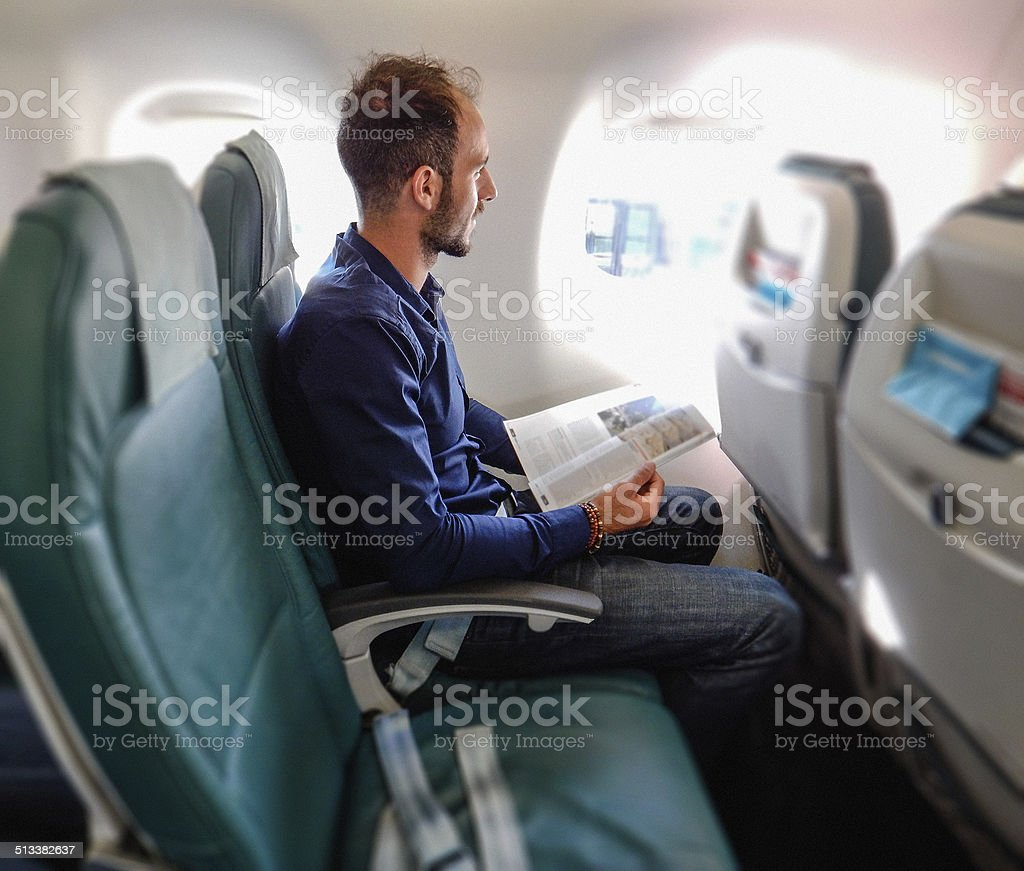 man inside an airplane reading a magazine