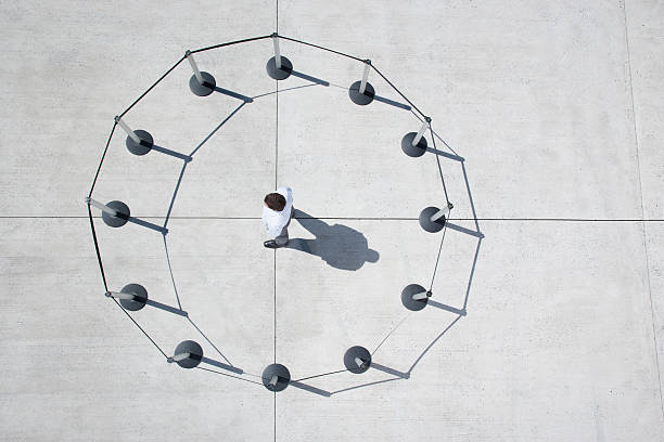 man inside circle of cordon posts - trapped stock pictures, royalty-free photos & images
