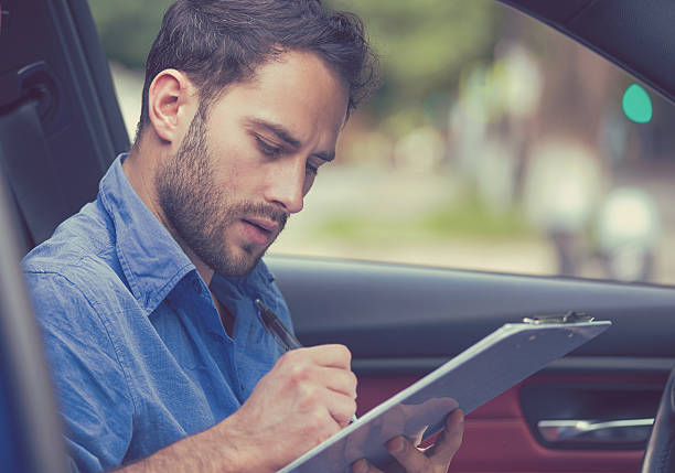 Man inside new car reading signing documents stock photo