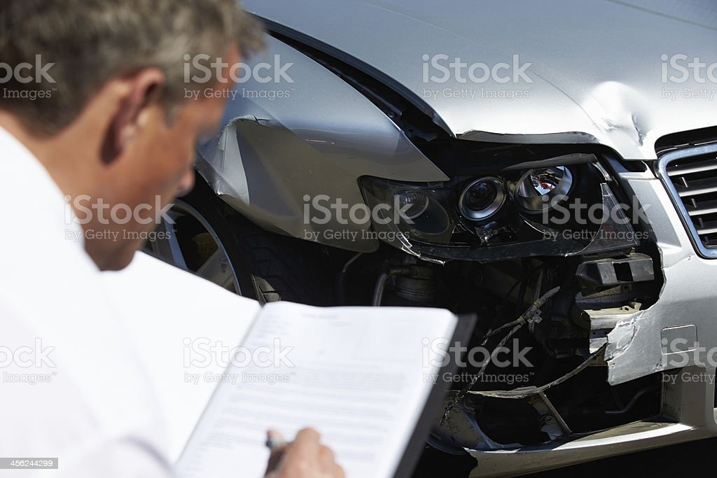 Man inspecting a car involved in a accident stock photo
