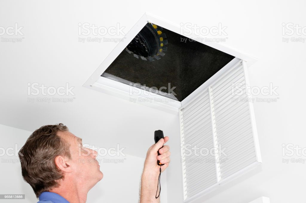Man Inspecting Air Intake Duct stock photo