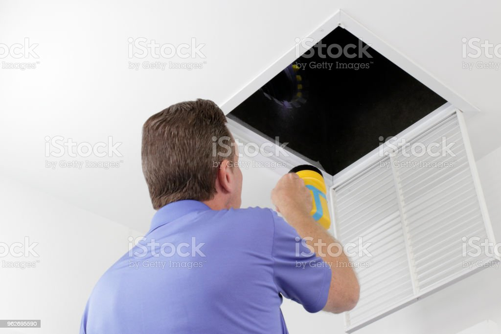 Man Inspecting an Air Duct with a Flashlight stock photo