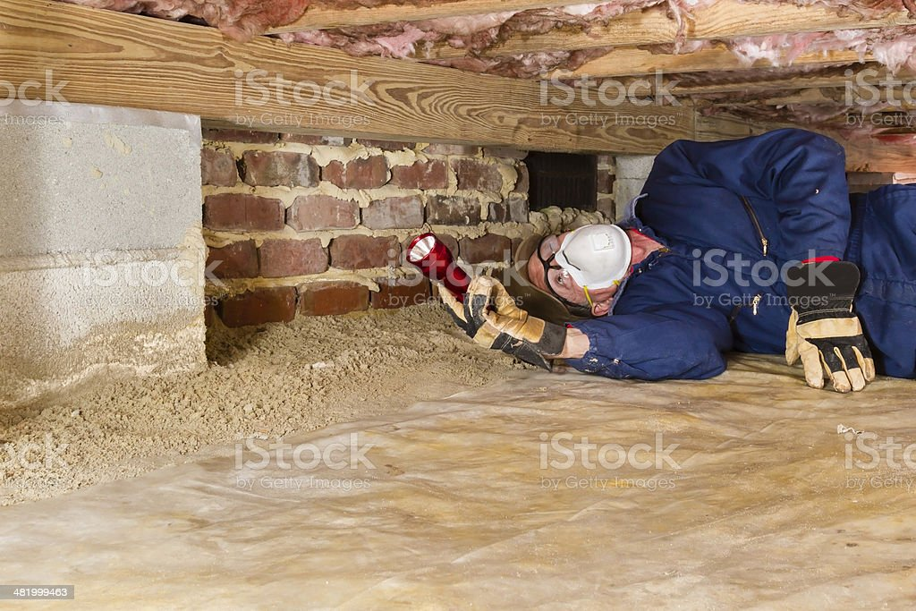 Man Inspecting For Termites In Crawl Space Stock Photo