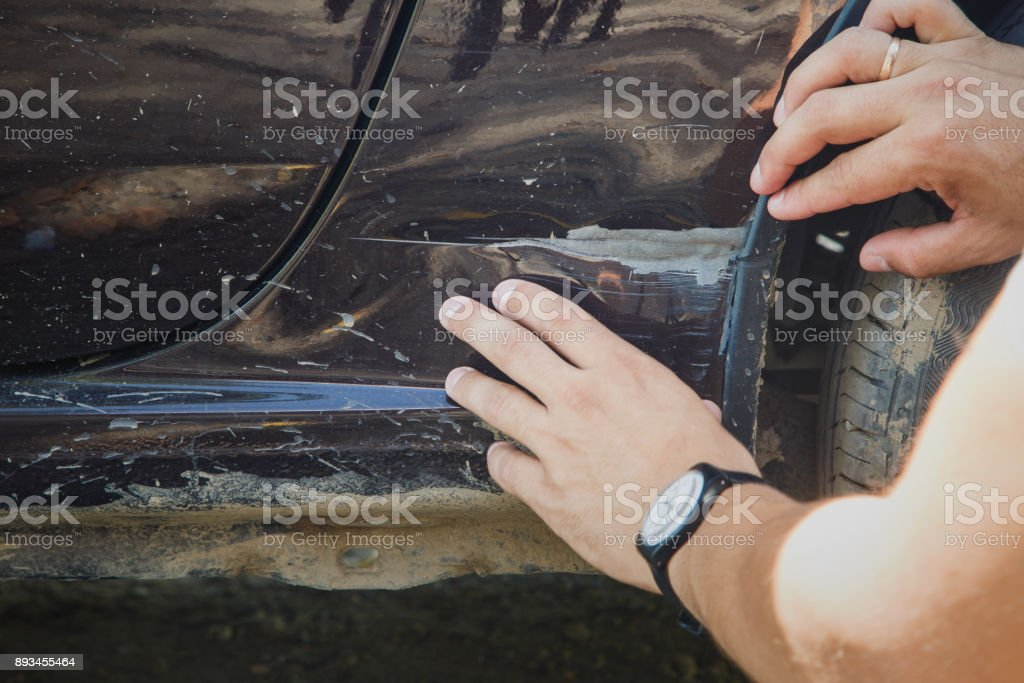 man inspects car t damage stock photo