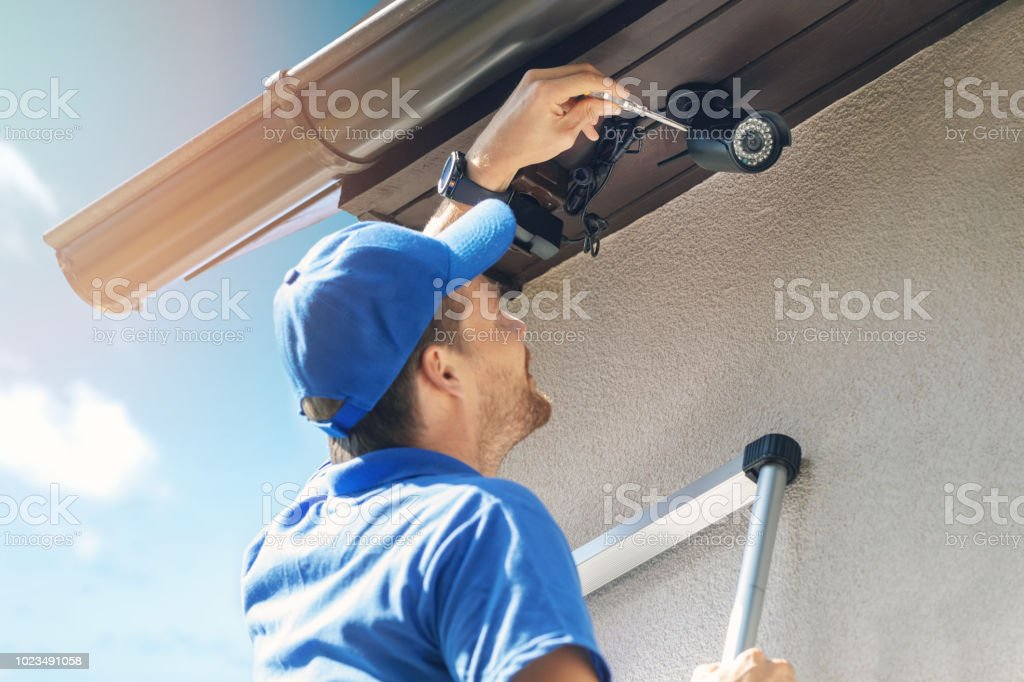 man install outdoor surveillance ip camera for home security stock photo