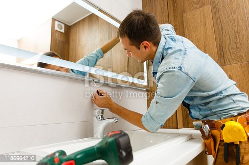 istock Man installing a mirror on wall in his renewed bathroom 1186964210