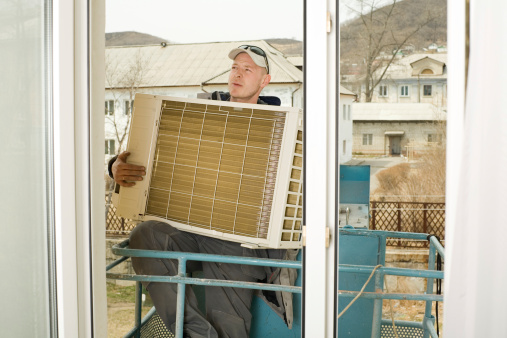 Man Installing A New External Air Conditioning Unit Stock Photo - Download Image Now