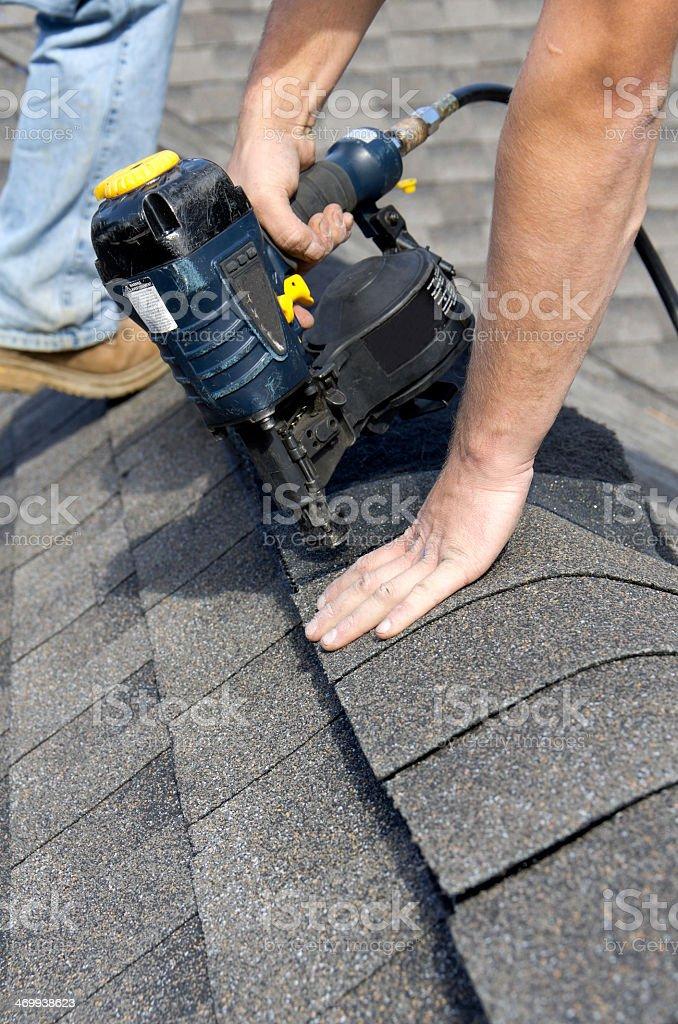 A man installing a shingles over a ridge stock photo