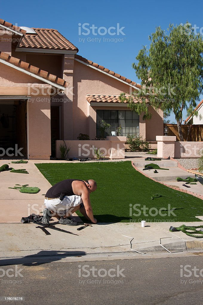 Man Installing Artificial Grass - Water Conservation royalty-free stock photo