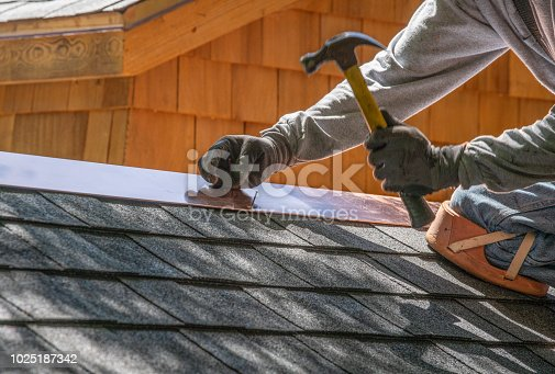 Installing new roof with  nail gun and shingles
