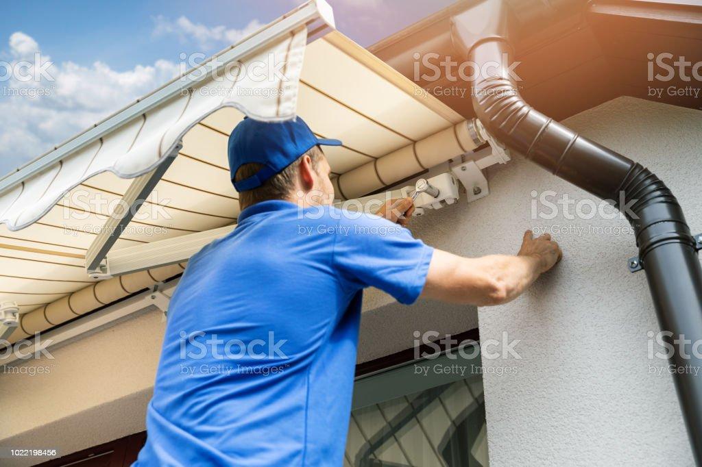 Mann, Markise über dem Balkonfenster auf Fassade Hauswand installieren – Foto