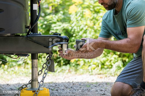 A man is Installing the camper trailer padlock during camping in summer.