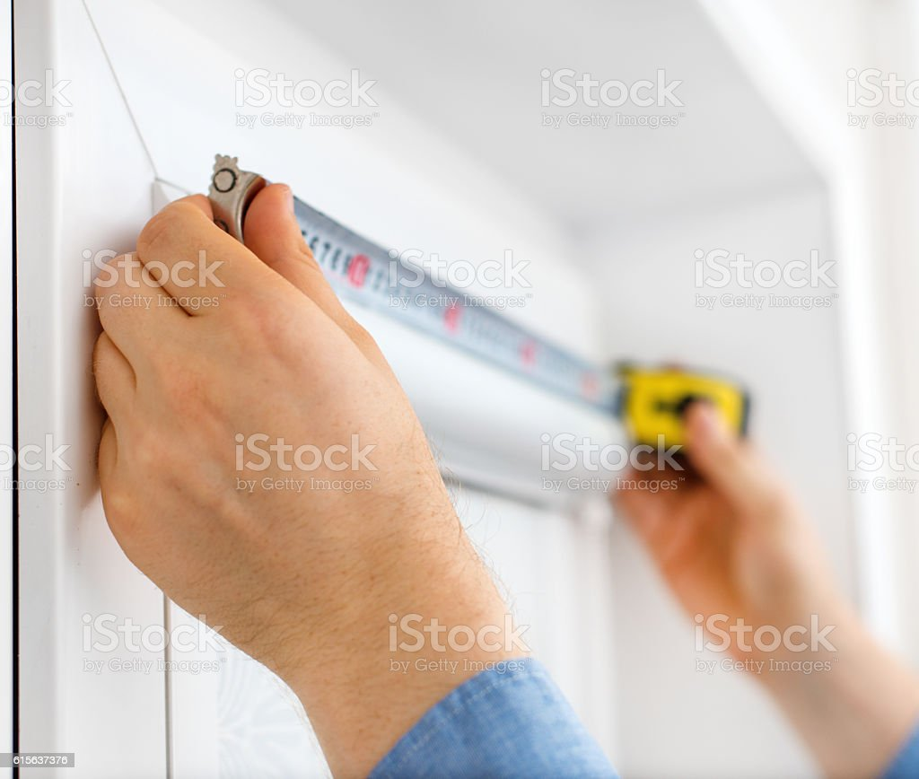 Man installing cassette roller blinds on windows. stock photo