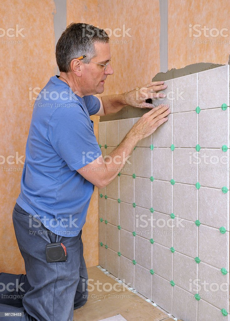 Man installing ceramic tile royalty-free stock photo