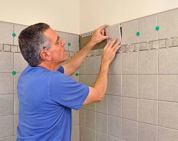Man installing ceramic tiles stock photo