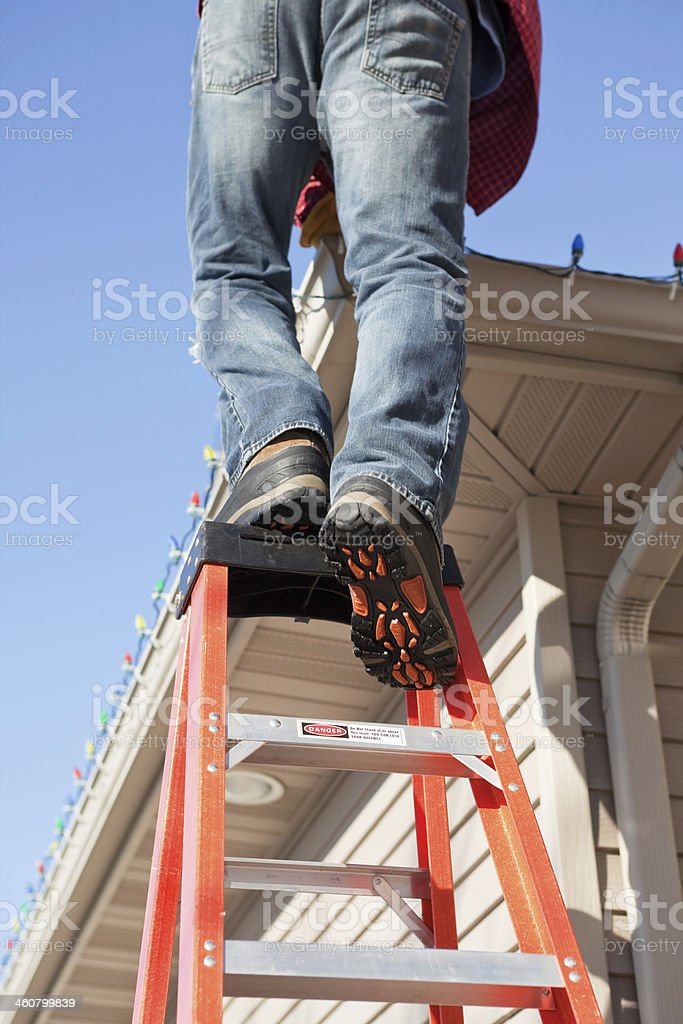 Man Installing Christmas Lights Stepping onto Ladder Top stock photo
