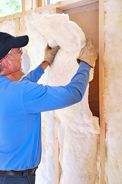 Man installing fiberglass insulation stock photo