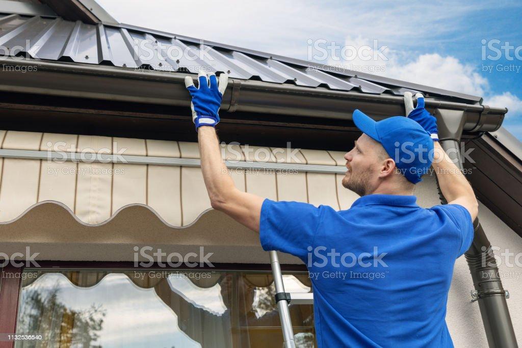 man installing house roof rain gutter system stock photo