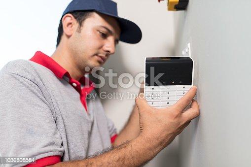 istock Man installing keypad of security alarm 1036808584
