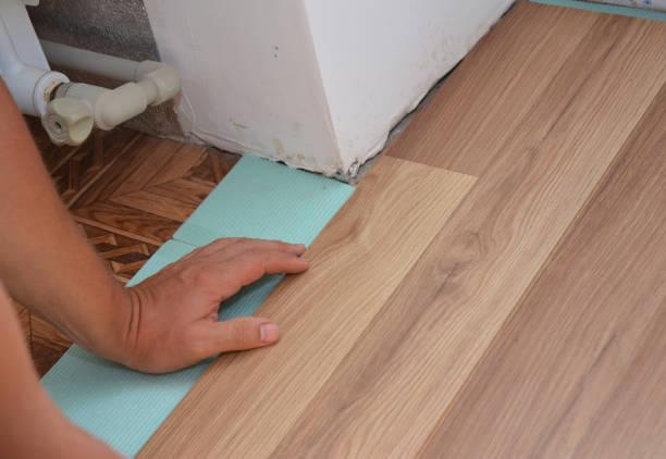 installation de planchers de bois laminés dans la problématique de l'homme. plancher en stratifié travailleur installation en bois. bricoleur fixant les panneaux stratifiés tout en rénovant une maison. - étage photos et images de collection