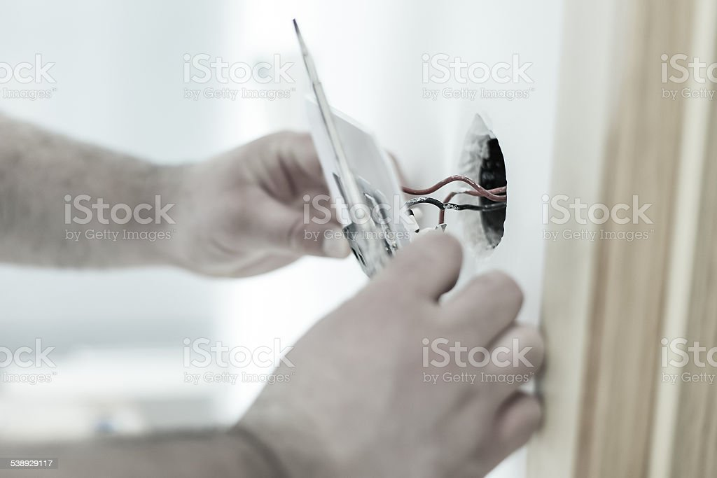 Man installing light switch stock photo