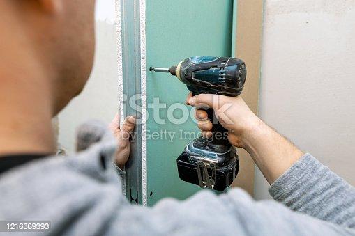 man installing moisture resistant drywall sheets for bathroom bulkhead