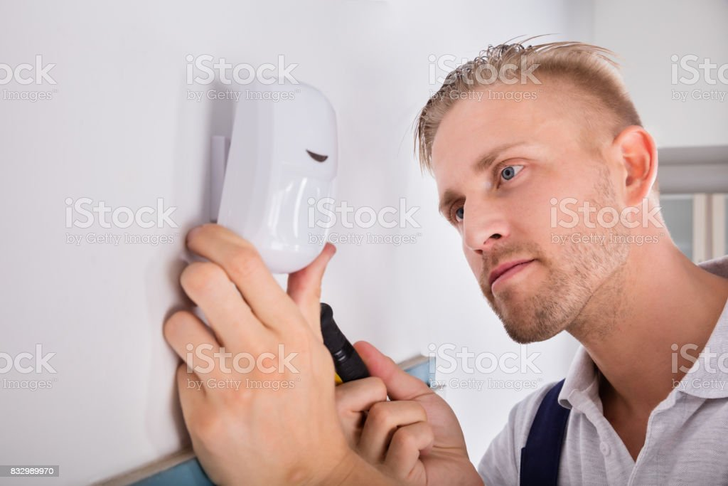 Man Installing Motion Detector For Security System - foto stock
