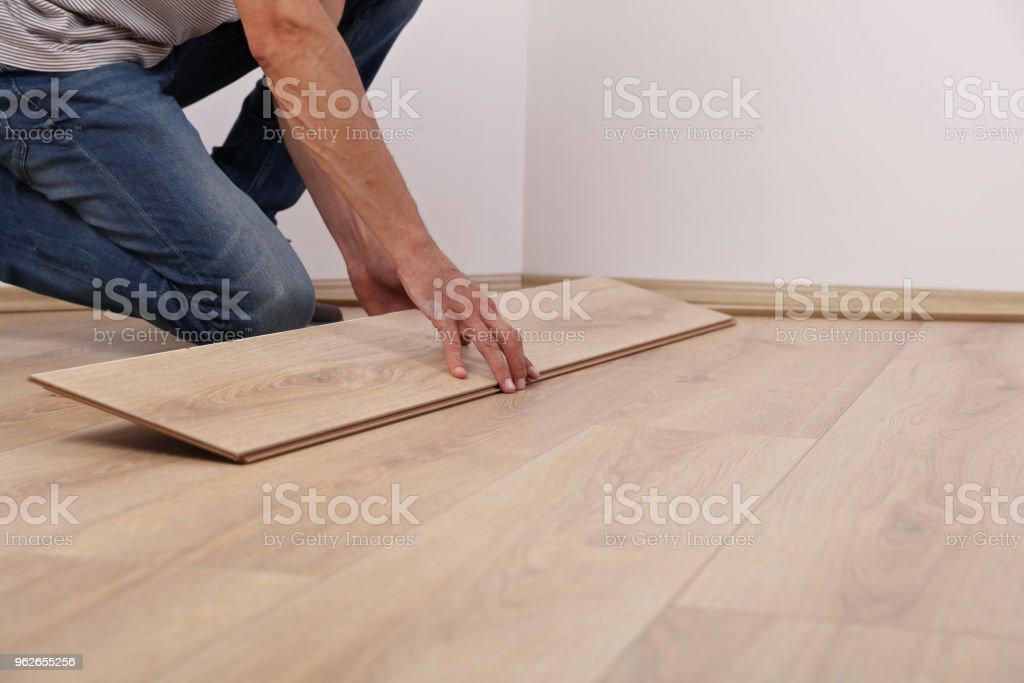 Man installing new laminated wooden floor close up stock photo