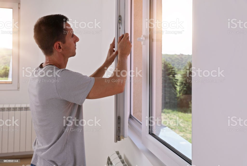 Man Installing New Windows In House stock photo