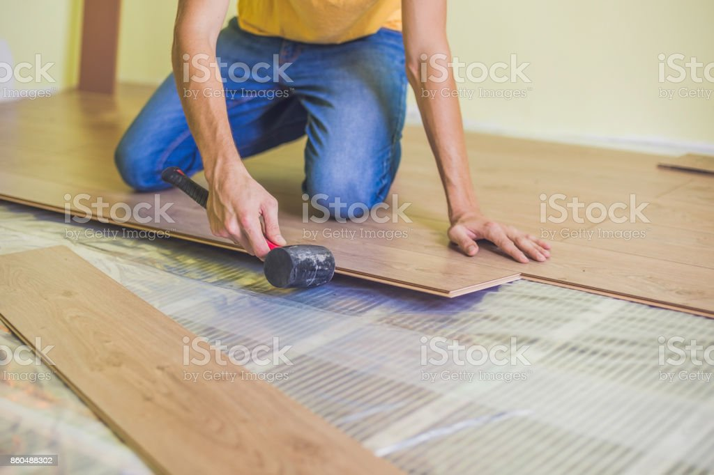 Man Installing New Wooden Laminate Flooring Infrared Floor Heating