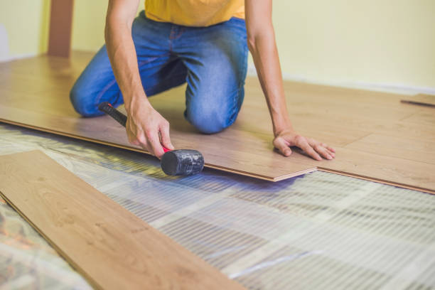 Man installing new wooden laminate flooring. infrared floor heating system under laminate floor stock photo
