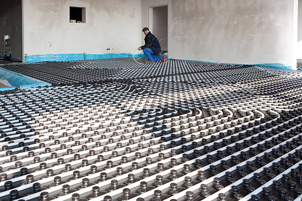 Man installing pipes for an underfloor heating system stock photo
