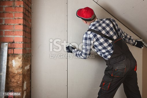 466705128 istock photo Man installing plasterboard sheet to wall for attic room construction 1142683834