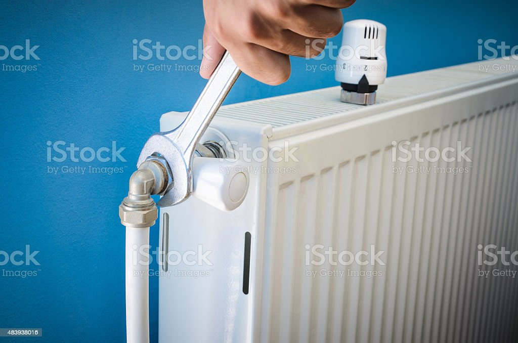 Man installing radiator valve close up stock photo