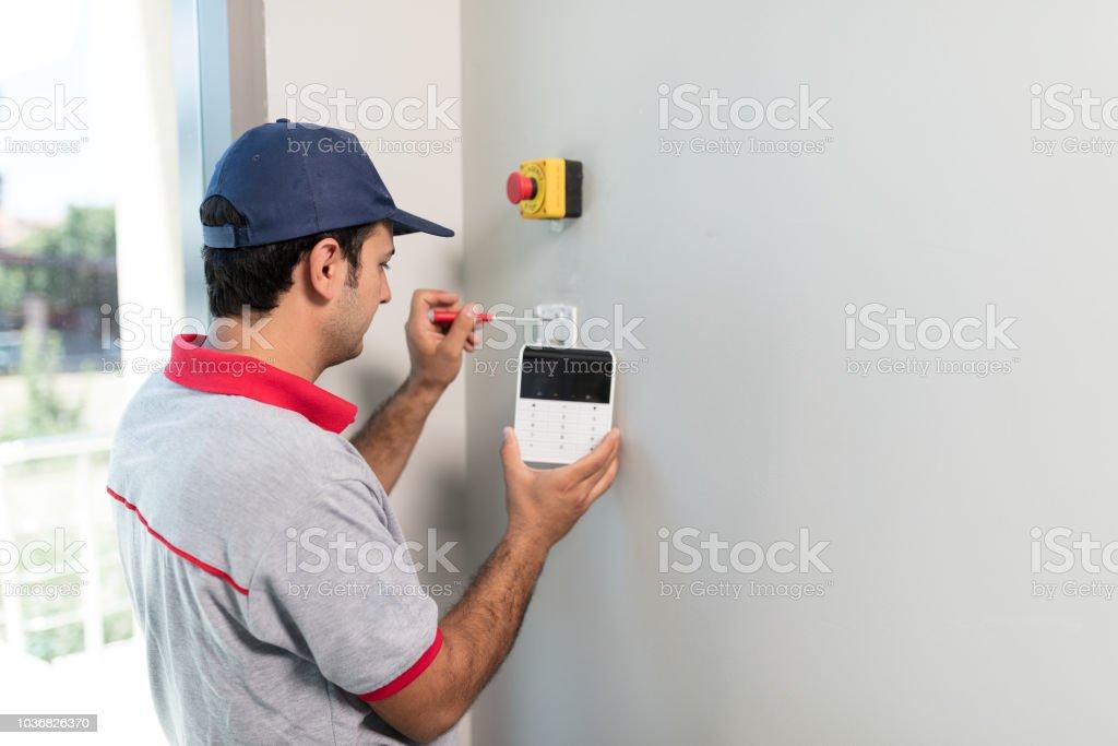 Man installing security alarm system stock photo