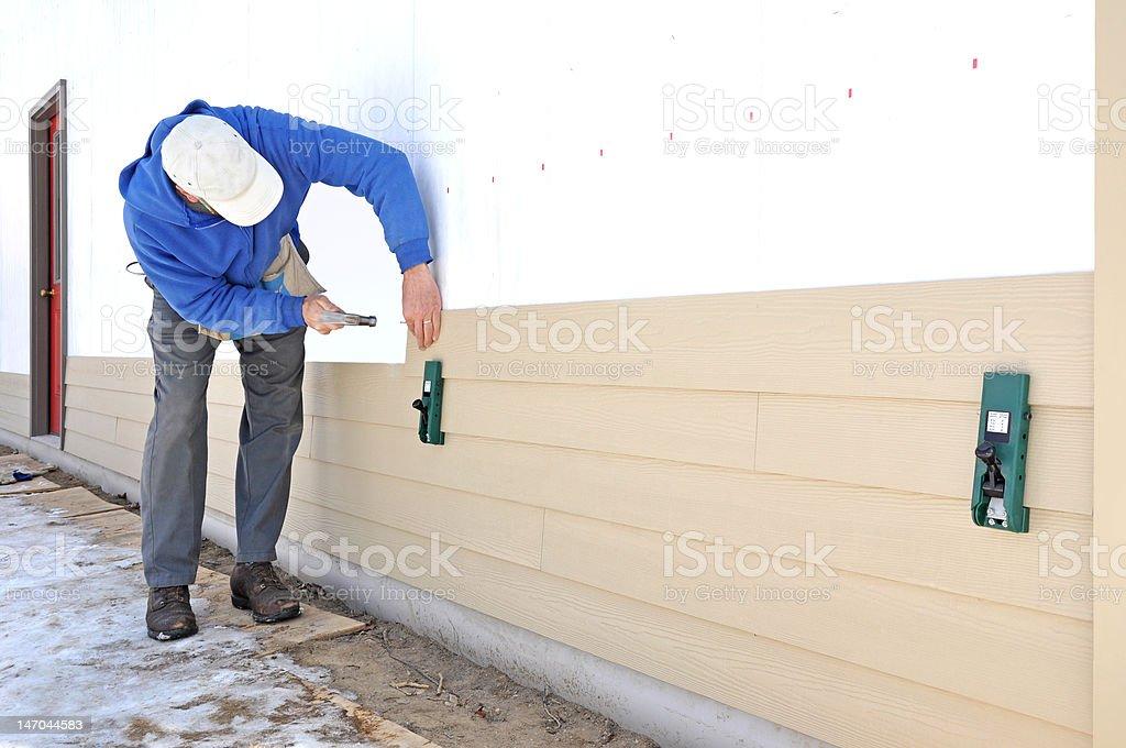 Man installing siding royalty-free stock photo